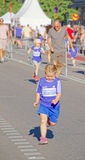 Young blonde girl running, other runners behind royalty free stock image