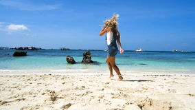Young blonde girl runs along the white beach with rocks and smiling. I feel free.