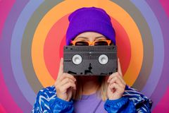 Young blonde girl in 90s sports jacket and hat royalty free stock image