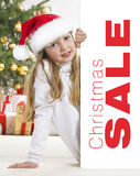 Young blonde girl in santa hat and red comforter b Royalty Free Stock Photography