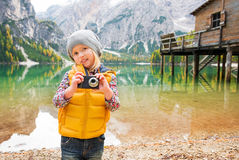 Young blonde girl on shores of Lake Bries holding a camera Royalty Free Stock Photos
