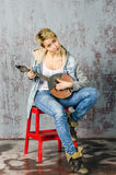 Young blonde girl with short hair in a denim jacket and jeans sits and looks with dombra. Young blonde girl with short hair in a denim jacket and jeans sits and royalty free stock images