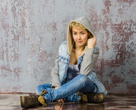 Young blonde girl with short hair in a denim jacket. And jeans sits and looks at the floor royalty free stock photography