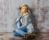 Young blonde girl with short hair in a denim jacket. And jeans sits and looks at the floor stock photo