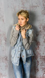 Young blonde girl with short hair in a denim jacket Stock Photo