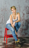 Young blonde girl with short hair in a denim jacket and jeans sits and looks. At the floor royalty free stock image
