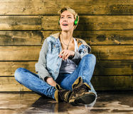 Young blonde girl with short hair in a denim jacket and jeans sits and looks. At the floor stock image