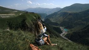 A young blonde girl sits on the grass on a background of mountains with a backpack and takes pictures of the mountains. On the phone. slowmotion stock footage