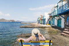 Young blonde girl sitting on a bench overlooking colourfull old houses in fishermen town of Klima on Milos island, Greece