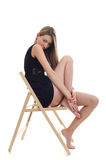 Young blonde girl sitting on a chair. Over white background royalty free stock photo