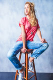 Young blonde girl sitting on a chair looking away Royalty Free Stock Images