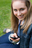 Young blonde girl sitting while sending a text Stock Photo