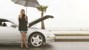 A young blonde girl stands beside her broken car under the umbrella. 