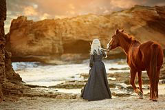 Young blonde girl stroking a brown horse stock photography