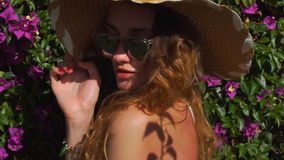 Young blonde girl in sunglasses and straw hat posing in the blooming garden stock footage