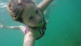 Young blonde girl in swimsuit swims under water on camera, Underwater shot stock video