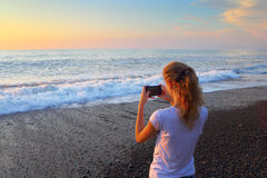 Young blonde girl takes pictures of the sunset. Stock Photos