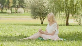 A young blonde girl is typing on the phone in a city park sitting on the grass. stock video footage