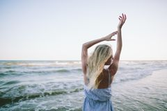 A young blonde girl is walking along the seashore Stock Photo