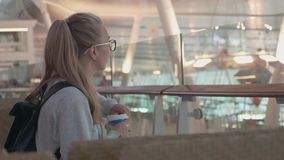 Girl Waiting in an Airport. Young blonde girl wearing glasses and holding passport, and ticket waiting for the flight at the airport. Woman drinking coffee stock footage