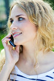 Young blonde girl whit smartphone at the park Royalty Free Stock Image