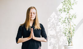 Young blonde girl in a white room doing meditation Stock Photos