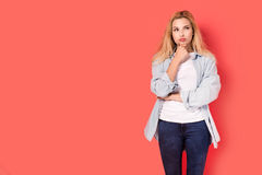 Young blonde girl with a wondering look on red background Stock Image
