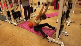 Young blonde girl working out in a gym with coach stock video