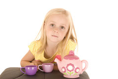 Young blonde girl in yellow top with folded arms and puffed upper Royalty Free Stock Photos