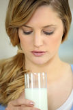 Young blonde with glass of milk Royalty Free Stock Images