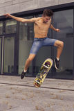 Young blonde guy jumping on skateboard in casual outfit in the u Stock Images