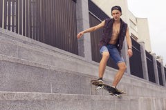 Young blonde guy on skateboard in casual outfit in the urban cit Stock Image