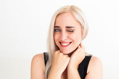 Young blonde-haired woman giving wink to camera Royalty Free Stock Images