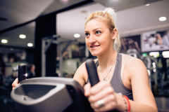 Young blonde is having cycling training at gym. Young blonde is having cycling training , exercise at gym Royalty Free Stock Image