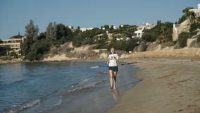 Young blonde with headphones runs along the beach near the ocean in the morning stock footage