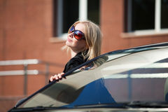Young blonde with a her car. Royalty Free Stock Photos
