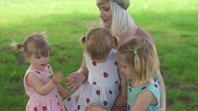 Young blonde hippie mother having quality time with her baby girls at a park blowing dandelion - daughters wear similar. Dresses with strawberry print - family stock video footage