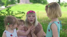 Young blonde hippie mother having quality time with her baby girls at a park blowing dandelion - daughters wear similar. Dresses with strawberry print - family stock footage