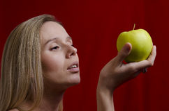 Young blonde holding an apple on red background Stock Photography