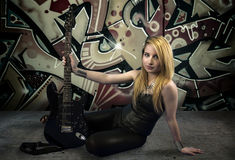 Young blonde holding a black guitar, over grafitti background Royalty Free Stock Photography