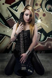 Young blonde holding a black guitar, over grafitti background Royalty Free Stock Photos