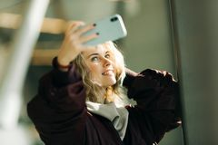 Young blonde in jacket makes selfie against background of window royalty free stock photo