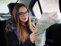 Young blonde woman in glasses exploring road map on back seat in car. Snow blizzard and rain outside. Stock Photo