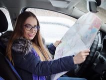 Young blonde woman in glasses exploring road map driver seat in car. Snow blizzard and rain outside. Royalty Free Stock Image