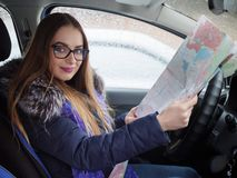 Young blonde woman in glasses exploring road map driver seat in car. Snow blizzard and rain outside. Stock Photo