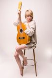 Young blonde lady in gray sweater sitting on chair and playing acoustic guitar Stock Photos