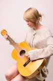 Young blonde lady in gray sweater sitting on chair and playing acoustic guitar. Picture presents Young blonde lady in gray sweater sitting on chair and playing Stock Photography
