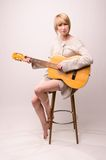 Young blonde lady in gray sweater sitting on chair and playing acoustic guitar. Picture presents Young blonde lady in gray sweater sitting on chair and playing Stock Images