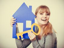 Young blonde lady holding symbols. Security safety home ownership concept. Young blonde lady holding symbols. Cheerful girl showing house key cutouts Stock Images