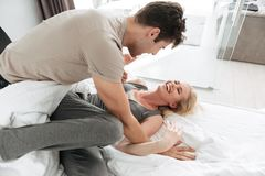 Young blonde lady laughing while playing with her man. Young blonde joyful lady laughing while playing with her lovely men in bed Stock Photography